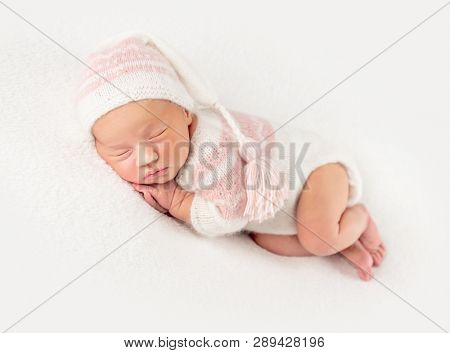 Pretty baby girl in creamy knitted suit and hat, isolated on white background