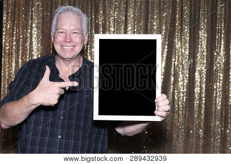 Man in a Photo Booth. A Man smiles and poses for photos to be taken in a photo booth.