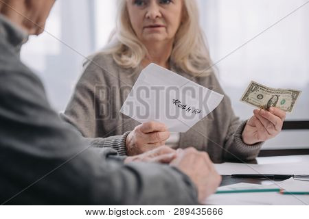 cropped view of senior couple holding envelope with roth ira lettering and dollar banknote poster