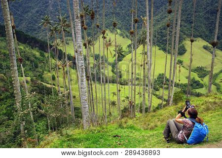 Young girl photographer taking pictures of Cocora valley, Salento, Colombia, South America