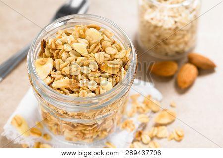 Homemade Baked Crunchy Oatmeal, Sliced Almond, Honey And Coconut Oil Breakfast Granola In Glass Jar,