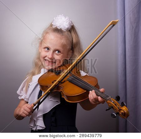 Happy Little Girl Playing The Violin On Gray Background