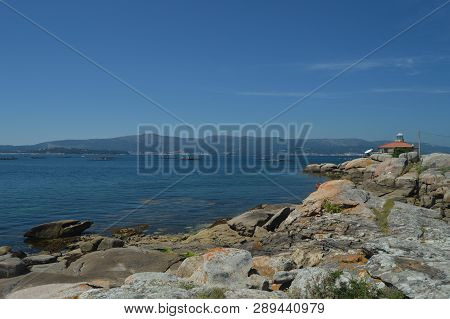 Estuary With Mussel Hatcheries In Its Interior In Front Of The Horse Point Lighthouse On Arosa Island. Nature, Architecture, History, Travel. August 18, 2014. Isla De Arosa, Pontevedra, Galicia, Spain. poster