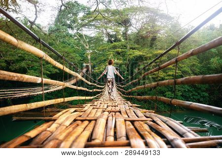Back View Of Young Woman On Suspension Wooden Bamboo Bridge Across Loboc River In Jungle. Vacation O