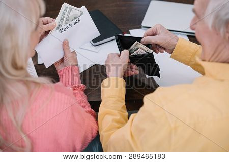 back view of senior couple holding money and envelope with roth ira lettering while sitting at table poster