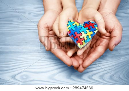 World Autism Awareness Day, Puzzle Or Jigsaw Pattern On Heart With Autistic Childs And Father Hands