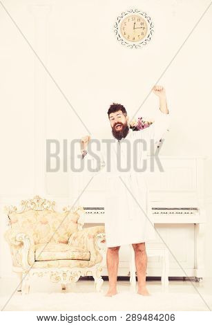 Happy Morning Concept. Hipster Enjoy Morning While Stretching Arms Near Piano And Old Fashioned Armc