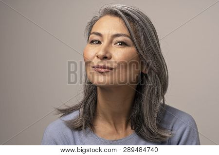 Charming Asian Woman With Grey Hair With Delicate Smile. Pretty Middle-aged Woman Making Duck Face W
