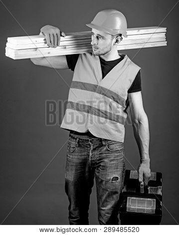 Carpenter, Woodworker, Labourer, Builder On Busy Face Carries Wooden Beams On Shoulder. Man In Helme