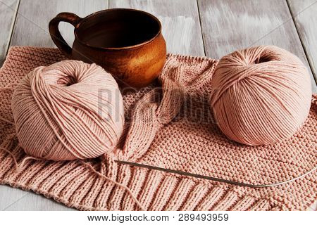 Original Exclusive Knitted Pattern Of Delicate Pink Yarn And Beautiful Clay Cup On Light Wooden Back
