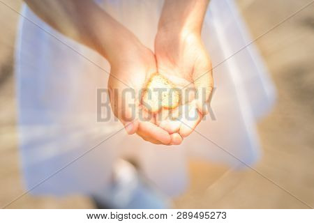 Little Girl Holds A Shining Heart In Her Hands. Light In The Hands Of Child. Concepts Of Miracle, Un