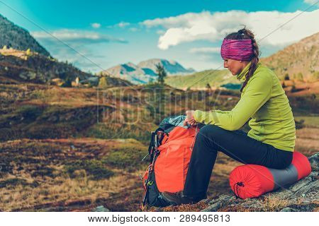 Trailhead Rest Stop. Young Caucasian Woman With Backpack On The Alpine Trail. Summer Time Hiking.