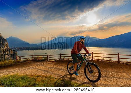 Cycling man riding on bike at sunrise mountains and Garda lake landscape. Cycling MTB enduro flow sentiero ponale trail track. Outdoor sport activity.