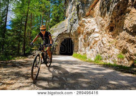 Woman mountain bike rider on electric bike, e-mountainbike rides up mountain trail. Woman ride on e-bike in Dolomites mountains landscape. Cycling e-mtb enduro trail track. Outdoor sport activity