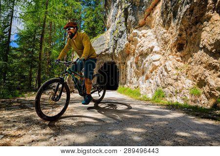 Single mountain bike rider on electric bike, e-mountainbike rides mountain trail. Man riding on e-bike in Dolomites mountains landscape. Cycling e-mtb enduro trail track. Outdoor sport activity.