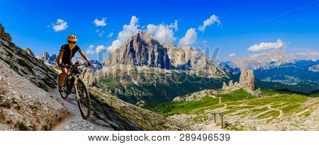 Cycling woman  riding on e-bike in Dolomites mountains landscape. Couple cycling MTB enduro trail track. Outdoor sport activity.