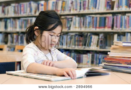 Cute Little Girl Reading Books At Library