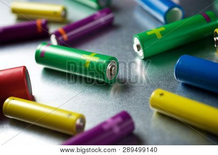 Many batteries on a metal table.