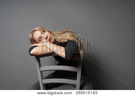 Bored Female Sitting Astride On Chair And Staring At Ceiling - Gray Background With Copy Space