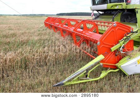 Machine harvesting the corn field in autumn poster