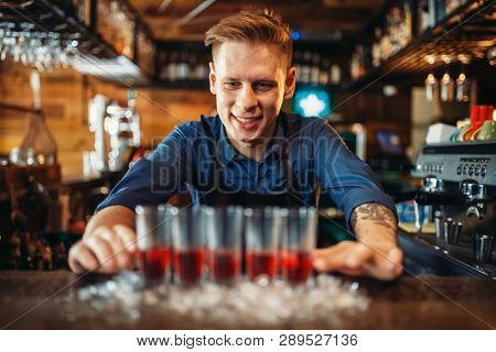Male bartender prepares four beverages in glasses