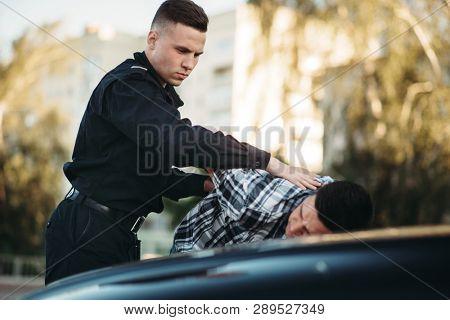 Police officer arrests the driver violator on road poster