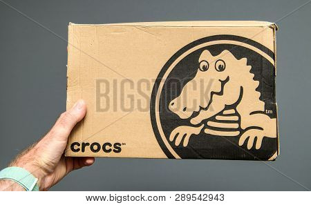 Paris, France - Jun 12, 2018: Man Hand Holding Freshly Delivered Crocs Shoes Cardboard Box Featuring
