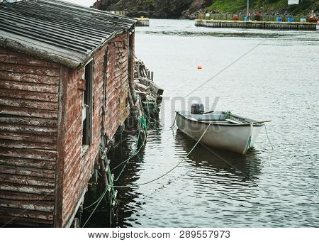 Small fishing boat tied up to a fishing shed in a safe harbor along the coast of Newfoundland, Canada.   poster