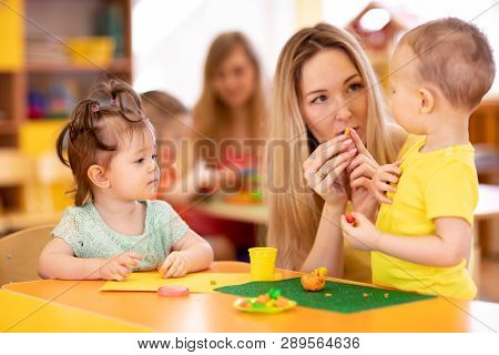 Nursery Babies Molded From Clay Toys. Teacher Plays With Children In Kindergarten