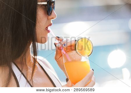 Close Up Photo Of Pretty Slim Woman With Long Dark Hair Standing Near The Pool With A Cocktail Weari
