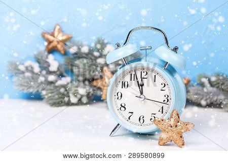 Blue Alarm Clock,  Branches Fir Tree  And Golden Stars On  Blue Textured  Background. Decorative Chr