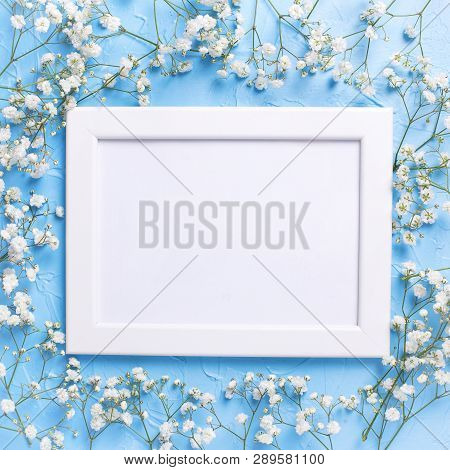 Empty  White Frame And  Fresh White Gypsofila  Flowers On Blue Textured Background. Top View. Flat L