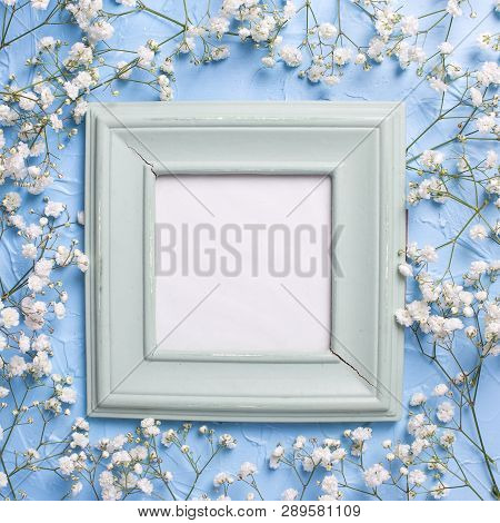 Empty  Vintage  Green Frame And  Fresh White Gypsofila  Flowers On Blue Textured Background. Top Vie