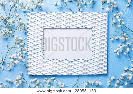 Vintage Empty Frame And  Fresh White Gypsofila  Flowers On Blue Textured Background. Top View. Flat