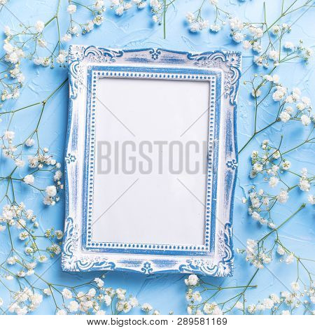 Empty  Vintage Frame And  Fresh White Gypsofila  Flowers On Blue Textured Background. Top View. Flat