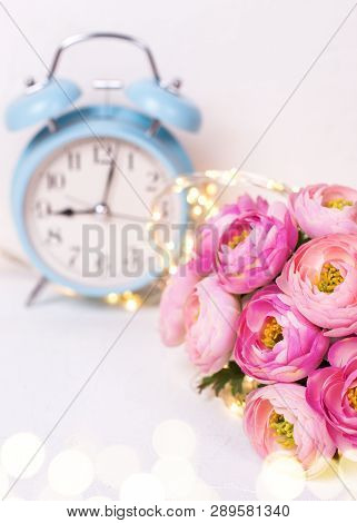 Background With  Pink Ranunculus Flowers And Blue Alarm Clock  On White Textured Background. Place F