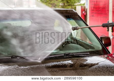 Cleaning Car With High Pressure Water. Close Up View