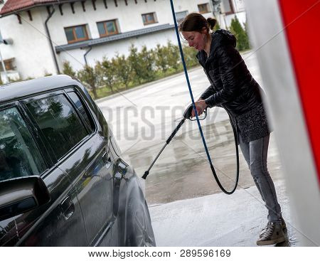 Smiling Woman Wahing The Car Using High Pressure Water