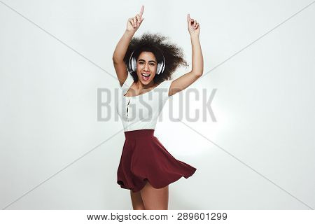 Music In Heart. Studio Portrait Of Happy Young African Woman Listening To Music And Dancing With Rai