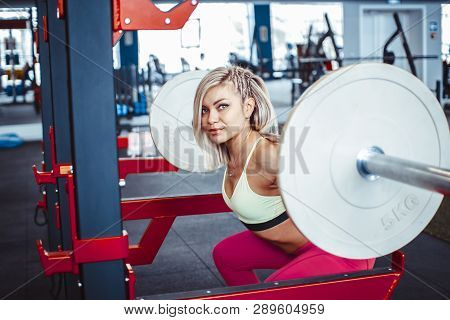 Attractive Young Sports Woman With Barbell. Doing Squats.