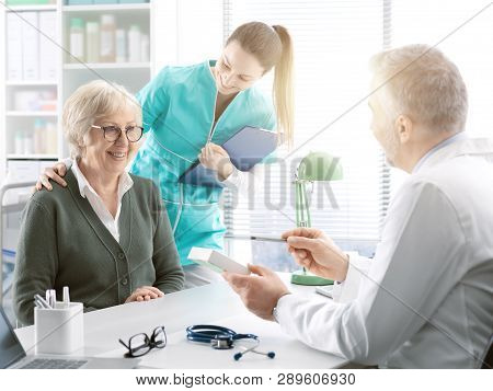 Professional Doctor Giving A Prescription Medicine To A Senior Patient