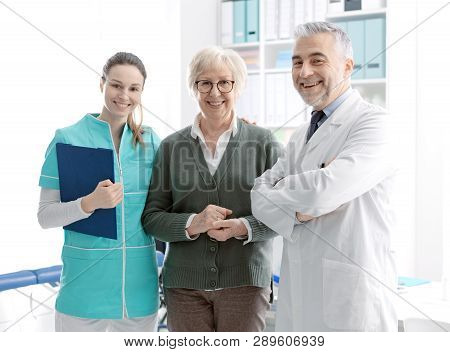 Senior Patient Posing With Medical Staff At The Clinic