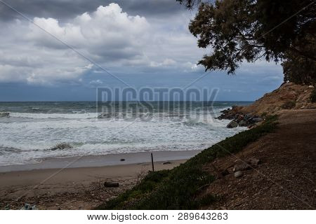 Coastline With A Sandy Beach. Green Color Of The Mediterranean Sea With Foamy Waves. Little Hill Wit