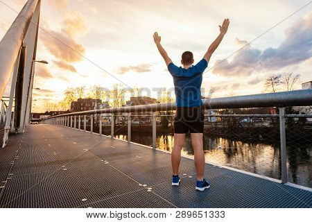 Rear View Of Young Man Winner Celebrating Sport Success As Raising Hands Up Standing On A Bridge Ove