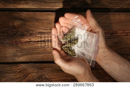 Man Holding Plastic Bags With Cocaine And Hemp Buds On Wooden Background, Top View. Space For Text
