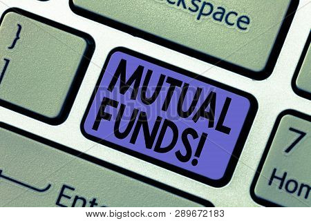 Handwriting text writing Mutual Funds. Concept meaning Investment Strategy to purchase shares with other investors Keyboard key Intention to create computer message pressing keypad idea. poster
