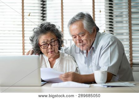 Stressed Asian Senior Couple Calculate Their Monthly Expense With Laptop Computer. Debts, Saving, Fi
