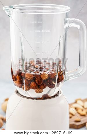 Blender and hazelnuts soaked in water. Making healthy vegan milk. Step by step recipe. poster