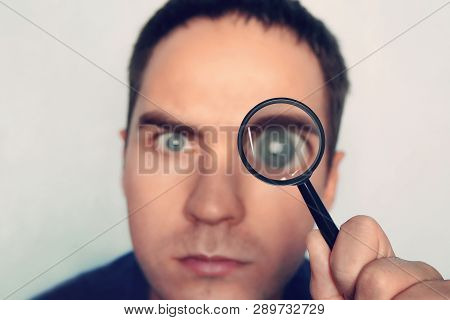 Man On White Background Curiously Looks Through The Magnifying Glass. Male Fuzzy Eye Magnified Throu