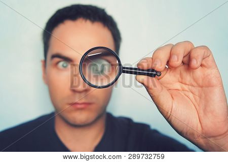 Male Hand Holding Magnifying Glass With Blurred Mans Eye On Foreground. Man Glanses Into The Lens An